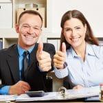 Geschäftsleute im Büro halten Daumen hoch