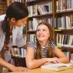 Female teacher and little girl in library