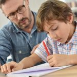 Teacher helping schoolboy with wRiting lesson