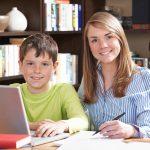 Female Tutor Helping Boy With Home Studies