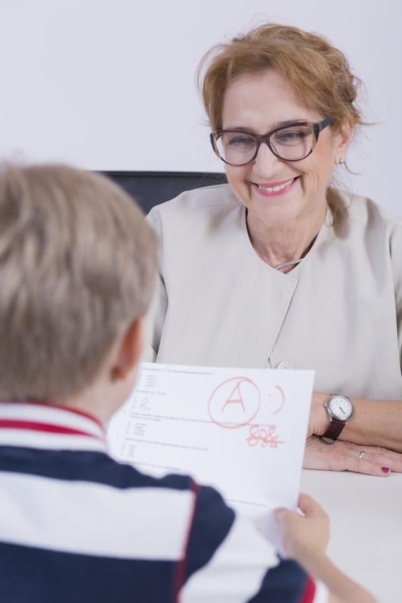 Das Bild zeigt eine ältere Nachhilfelehrerin beim Einzelunterricht mit einem Schüler, der einen guten Test zurückbekommen hat